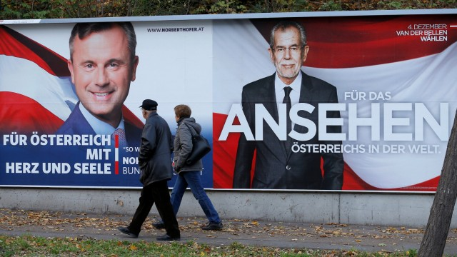 People pass presidential election campaign posters of Hofer and Van der Bellen in Vienna