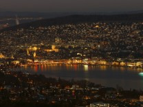 A night view shows the city of Zurich and Lake Zurich