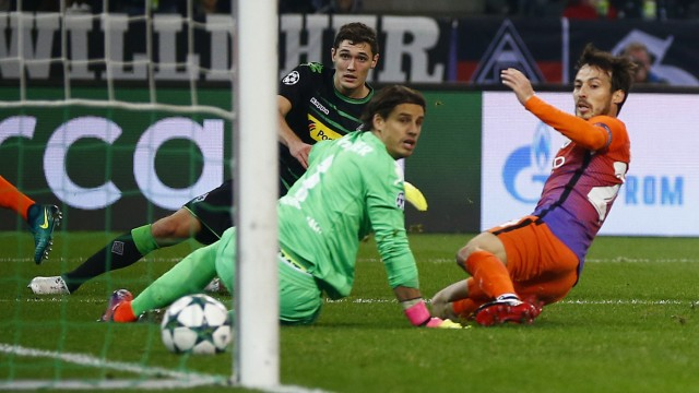 Manchester City's David Silva scores their first goal as Borussia Monchengladbach's Andreas Christensen and Yann Sommer (C) look on