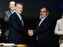 Colombia's President Juan Manuel Santos and Marxist FARC rebel leader Rodrigo Londono known as Timochenko shake hands after signing a peace accord in Bogota
