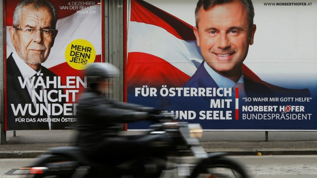 A motorcyclist passes presidential election campaign posters of Van der Bellen and Hofer in Vienna