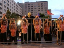 Protesters with their bodies painted depicting blood are seen as they attend a demonstration to support International Day for the Elimination of Violence Against Women in Santiago