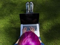 Young woman with dyed hair sitting on a meadow using laptop top view model released Symbolfoto PUBL