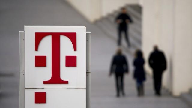 People walk past the logo of German telecommunications giant Deutsche Telekom AG seen at the Telekom's headquarters in Bonn