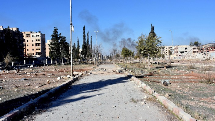 Smoke rises behind a damaged street in Hanano housing district after government forces took control of the area in Aleppo