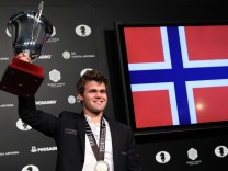 World Chess Champion Magnus Carlsen of Norway raises a trophy after winning the 2016 World Chess Championship match in New York