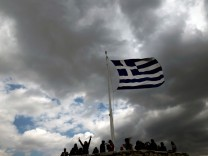People are silhouetted under a fluttering Greek national flag atop the archaeological site of the Athens Acropolis