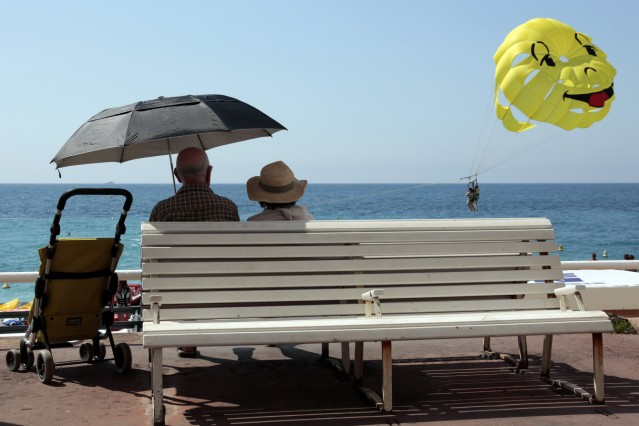 Two elderly people look at a parascending during a sunny summer day in Nice