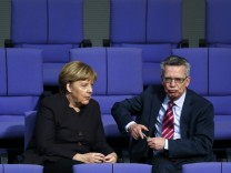 German Chancellor Merkel speaks with Interior Minister de Maiziere after a session of the German lower house of parliament, the Bundestag, in Berlin