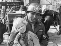 Farbiger US-Soldat mit einem Kind auf den Knien