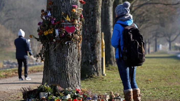 A woman looks at flowers and messages attached on a tree near the site where a 19-year-old female student was found dead in Freiburg