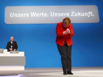 German Chancellor and leader of the conservative CDU Merkel reacts after her speech at the CDU party convention in Essen