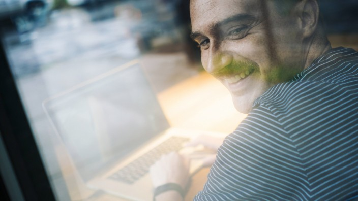 Smiling man using laptop model released Symbolfoto PUBLICATIONxINxGERxSUIxAUTxHUNxONLY GIOF01595