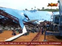 People stand near the remains of a church which collapsed during a service in the southern city of Uyo in Akwa Ibom state, Nigeria in this still image from video