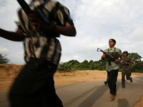 Female Tamil Tiger rebels run on a street as they head back to base after an overnight guard duty in Kilinochchi