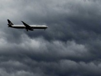 A plane flies under rain clouds near Haarlem