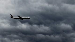 A plane flies under rain clouds near Haarlem