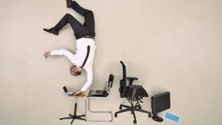 Businessman doing handstand while working on laptop model released Symbolfoto PUBLICATIONxINxGERxSUI