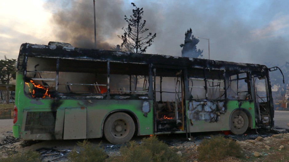 A bus is set on fire while en route to evacuate ill and injured people from the besieged Syrian villages of al-Foua and Kefraya, after they were attacked and burned, in Idlib province