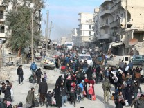 Rebel fighters and civilians gather near damaged buildings as they wait to be evacuated from a rebel-held sector of eastern Aleppo