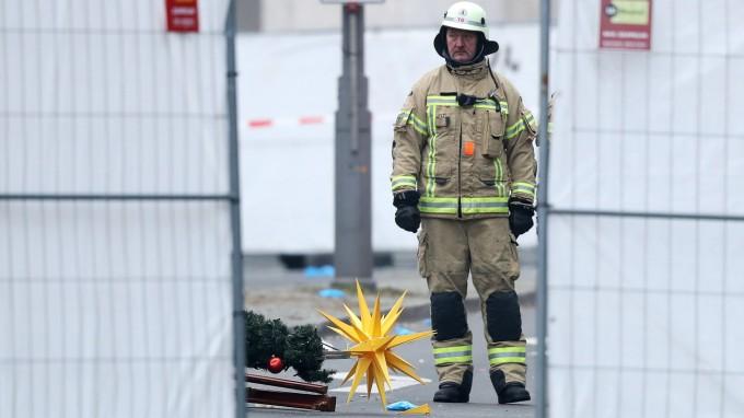 Eine Rettungskraft steht neben dem umgestürzten Weihnachtsbaum, der von dem LKW zu Fall gebracht wurde: