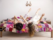 Two best friends lying on bed with legs in the air listening music with headphones model released Sy