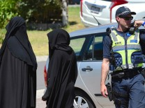 Women stand next to a policeman blocking a road where police officers are searching a house in the Melbourne suburb of Meadow Heights, Australia
