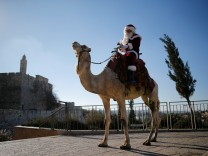 Kassissieh wears a Santa Claus costume as he rides a camel during an annual Christmas tree distribution by the Jerusalem municipality, in Jerusalem's Old City
