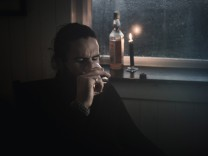 A man sitting in the dark by a window in candlelight drinkin from a small glass A bottle beside him