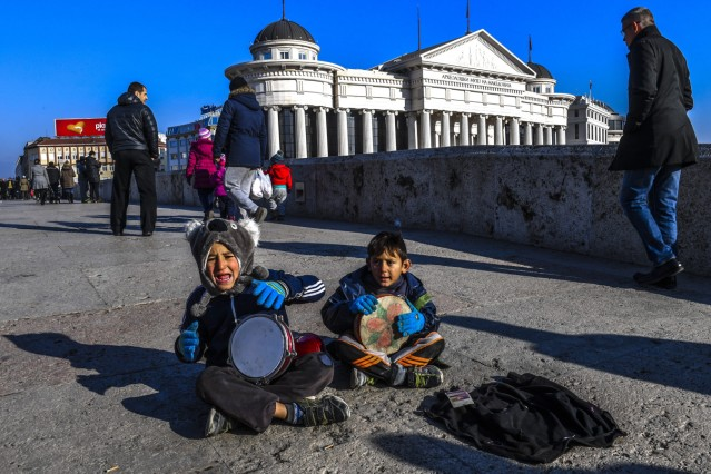 Small children play on their instrument and beg at the old Stone