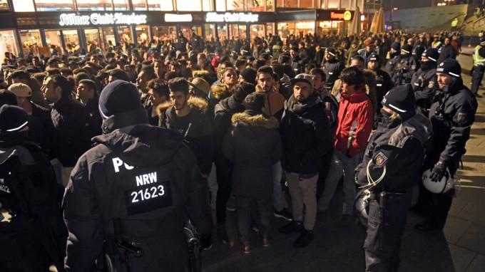 Am Kölner Hauptbahnhof umringen Polizisten eine Gruppe Männer. (Foto: dpa)