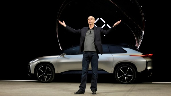 Nick Sampson, senior vice president of product R&D and engineering at Faraday Future, speaks in front of a Faraday Future FF 91 electric car during an unveiling event at CES in Las Vegas