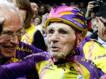 French cyclist Robert Marchand, aged 105, reacts after he rode 22.528 km (14.08 miles) in one hour to set a new record at the indoor Velodrome National in Montigny-les-Bretonneux