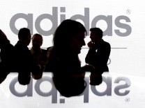 Shareholders' of Adidas Group are silhouetted in front of the logo before shareholder meeting in Fuerth