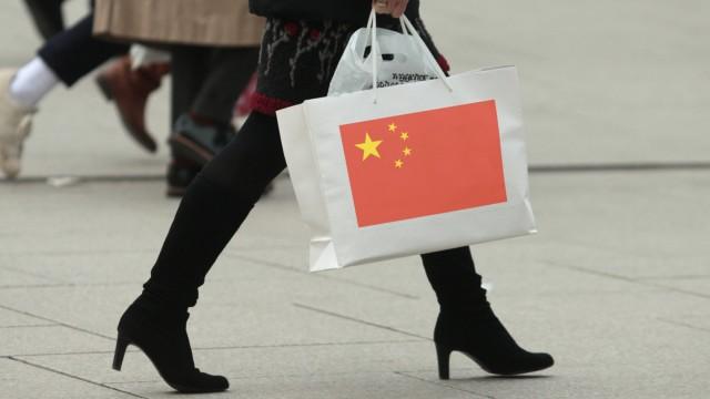Symbolbild privater Konsum und Kaufkraft Frau mit Stiefeln trägt eine Tragetasche mit Flagge China