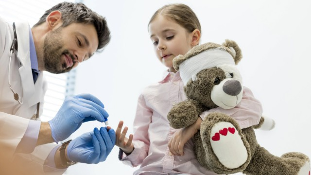 Doctor treating girl holding teddy model released Symbolfoto property released PUBLICATIONxINxGERxSU