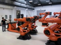 FILE PHOTO: A staff member stands next to robots at a plant of Kuka Robotics in Shanghai