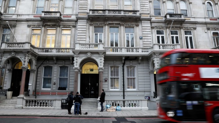 People stand outside the building housing the offices of Orbis Buiness Intelligence (C) where former British intelligence officer Christopher Steele works, in central London