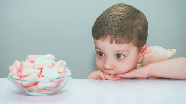 Boy hugging toy, looking at bowl of marshmallows; Getty Images Creative RF-2.177355581-HighRes-farbig