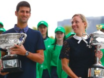 Current Australian Open tennis champions Serbia's Novak Djokovic and Germany's Angelique Kerber walk together as they hold the tournament trophies ahead of the official draw ceremony in Melbourne, Australia