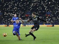 Fans light up their phones for former Chelsea and Leicester player Alan Birchenall as Chelsea's Marcos Alonso and Leicester City's Marc Albrighton challenge for the ball