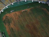 Aerial view of Maracana Stadium shows seats missing and the turf dry, worn and filled with ruts and holes in Rio de Janeiro