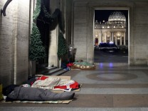 Homeless people sleep in passageway near St. Peter's square in Rome