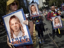 FILE PHOTO --  People hold signs calling for the release of imprisoned wikileaks whistleblower Chelsea Manning while marching in a gay pride parade in San Francisco, California