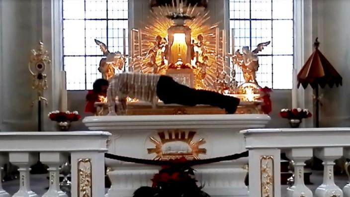 """Alexander Karle beiseinem Kunstprojekt """"Pressure to Perform"""" (""""Leistungsdruck""""), bei dem er Liegestütze auf dem Altar der katholischen Kirche St. Johann in Saarbrücken ausführte."""