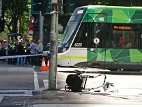 The wreckage of a pram is seen on the footpath in front of a tram on a main street after a car hit pedestrians in central Melbourne, Australia
