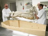 Schweinemumie, mumifiziertes Schwein wird im Klinikum Schwabing in die in die Kernspin-Röhre geschoben.