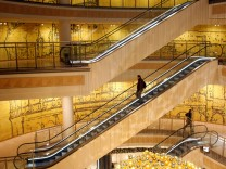 A customer uses the escalators in a shopping mall in Essen