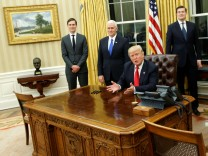 Trump, flanked by Kushner, Pence, Porter and Priebus, welcomes reporters into the Oval Office for him to sign his first executive orders at the White House in Washington