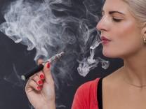 Junge attraktive blonde Frau raucht eine e zigarette als Portrait Junge attraktive blonde Frau rauch